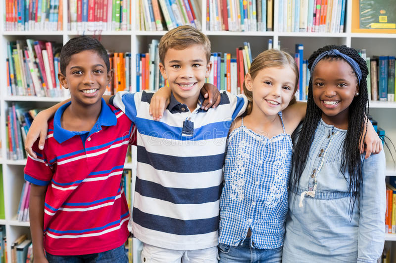 Smiling school kids standing with arm around in library royalty free stock image