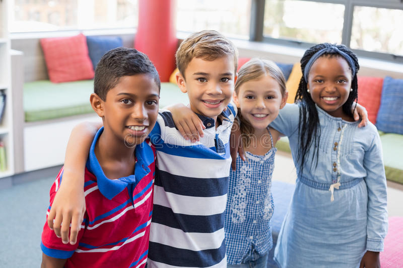 Smiling school kids standing with arm around in library stock photo