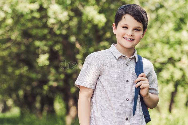 Smiling schoolboy with backpack looking. At camera outdoors royalty free stock photo