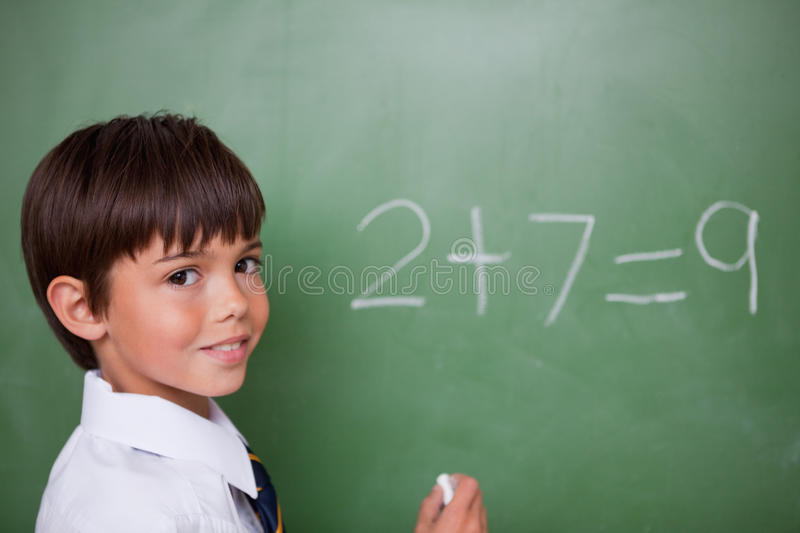 Smiling schoolboy writing an addition royalty free stock image