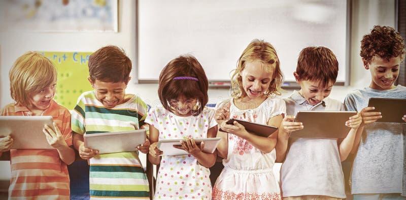 Smiling schoolchildren using digital tablets stock photography