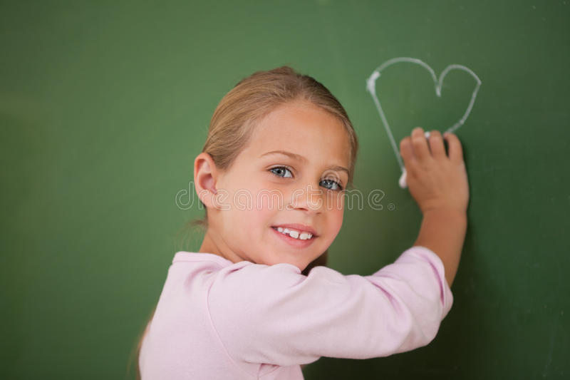 Smiling schoolgirl drawing a heart. On a blackboard royalty free stock photos