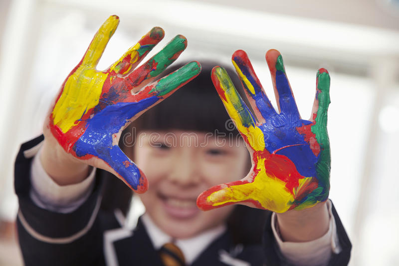 Smiling schoolgirl finger painting, close up on hands royalty free stock image