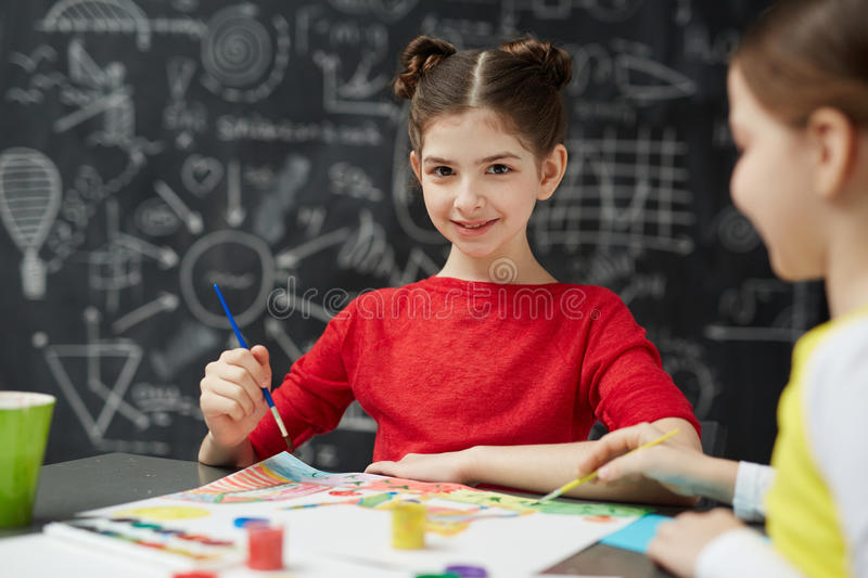 Smiling Schoolgirl Painting in Art Class. Portrait of pretty little girl looking at camera while painting pictures with friend during art lesson in school stock photo
