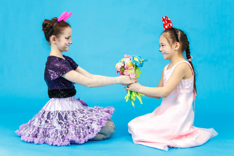 Smiling schoolgirl presents a bouquet of toy flowers. To her classmate on blue background royalty free stock photos
