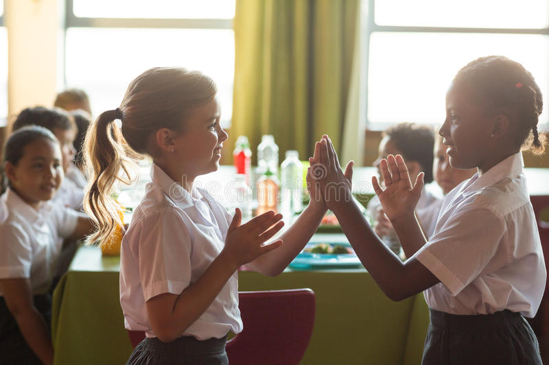 Smiling schoolgirls playing clapping game royalty free stock photos