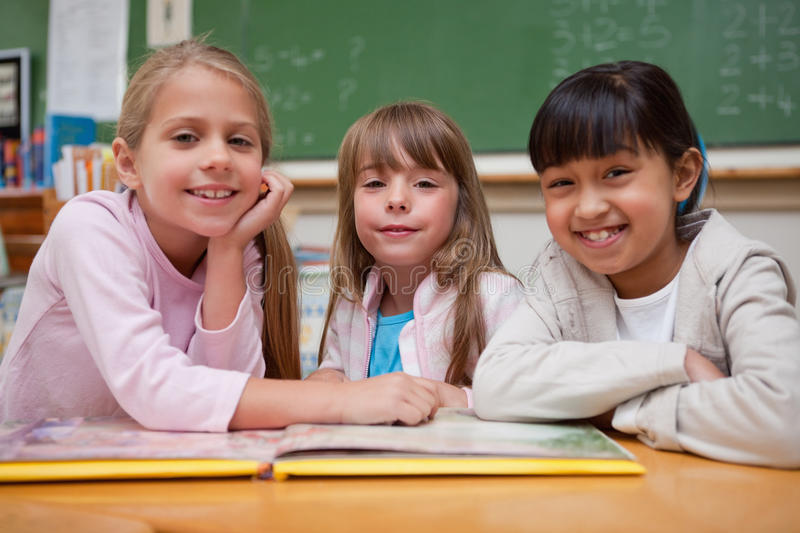 Smiling schoolgirls reading a fairy tale to their classmate royalty free stock photos