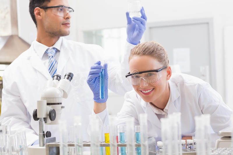 Smiling scientists examining test tube and beaker royalty free stock photo