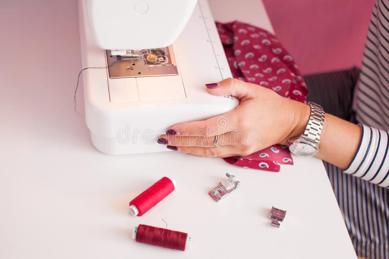 Smiling seamstress and her hand close up in workshop. Young dressmaker woman sews clothes on sewing machine. stock images