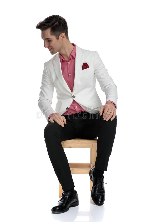 Smiling seated young businessman looks down to side stock photos