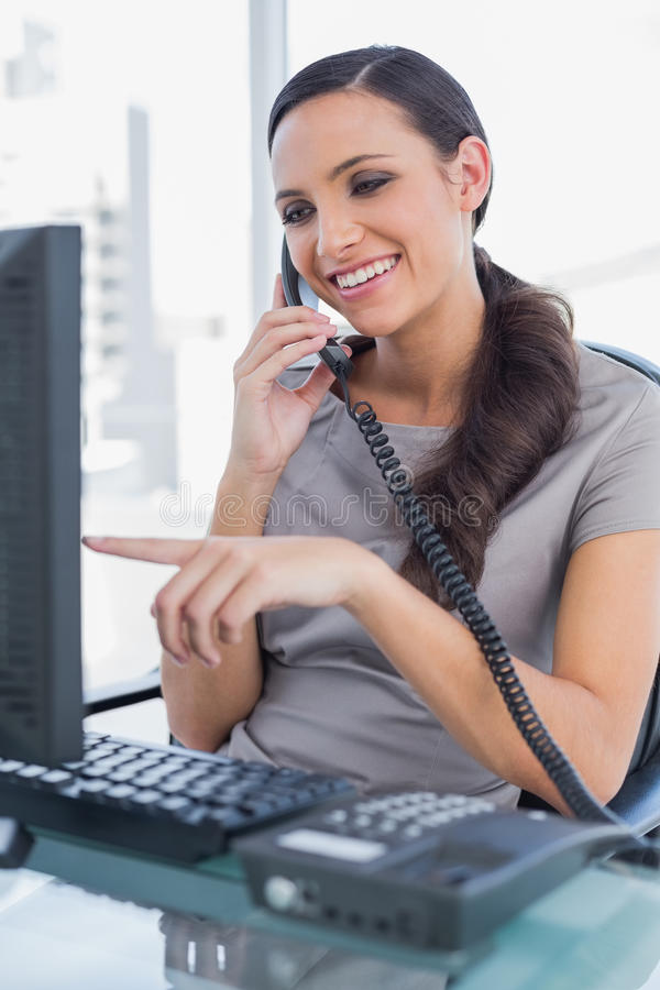 Smiling secretary answering land line and pointing at computer screen royalty free stock image