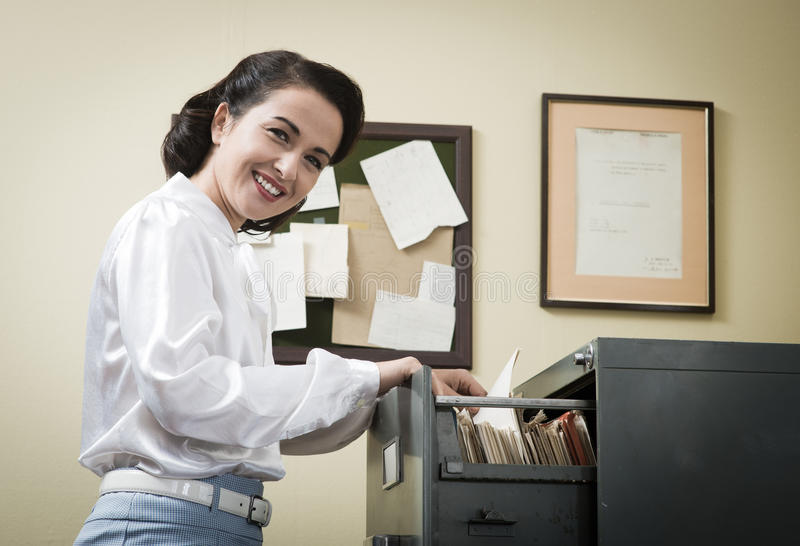 Smiling secretary searching files in the filing cabinet. Smiling vintage secretary searching files in the filing cabinet drawers stock photo