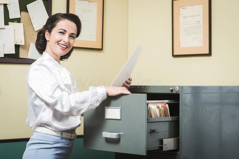 Smiling secretary searching files in the filing cabinet. Smiling vintage secretary searching files in the filing cabinet drawers royalty free stock image