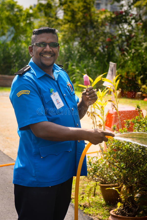 Download Smiling Security Guard Man With Ice-cream Waters A Lawn Editorial Stock Image - Image: 98764444