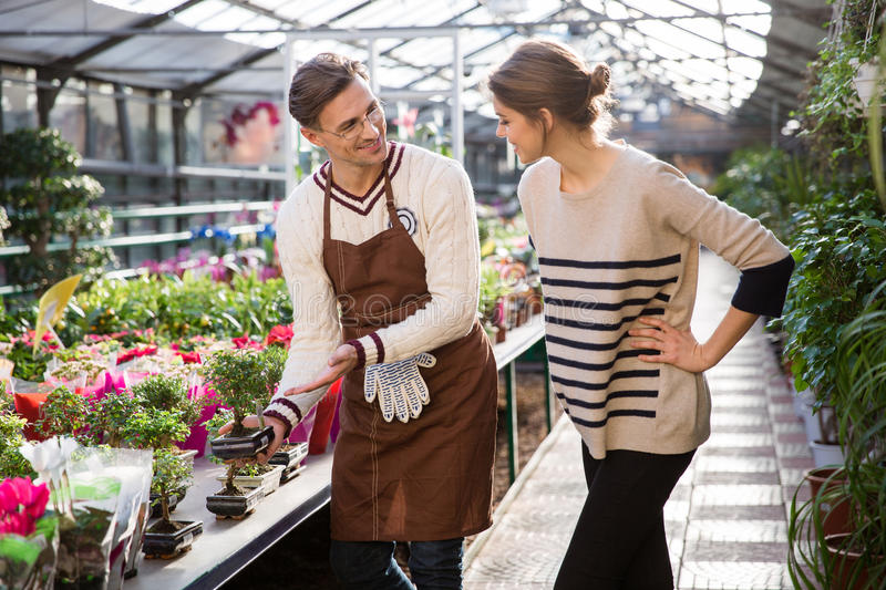 Smiling seller showing small bonsai tree to young woman. Smiling seller in brown apron and glasses showing small bonsai tree to young women in greenhouse royalty free stock images