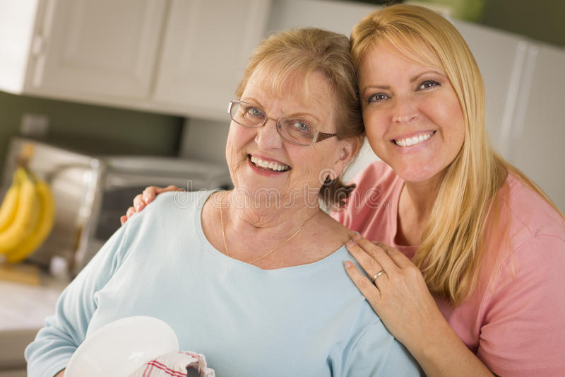 Senior Adult Woman and Young Daughter Portrait in Kitchen. Smiling Senior Adult Woman and Young Daughter At Sink in Kitchen royalty free stock images