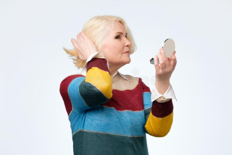 Smiling senior blond woman with mirror over white background royalty free stock images