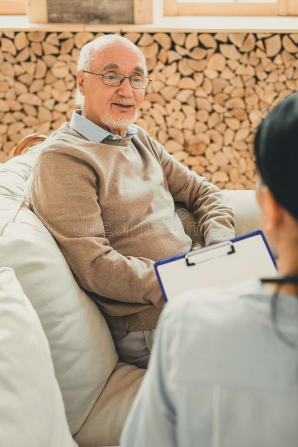 Smiling senior in brown sweater during doctor appointment. Pensioner questionable looking. Smiling senior in brown sweater during routine doctor appointment in stock photos