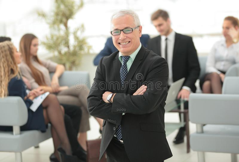 Smiling senior businessman on the background of business team stock images