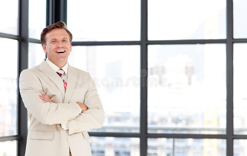 Smiling senior businessman with folded arms. Senior businessman with folded arms smiling at the camera royalty free stock photography