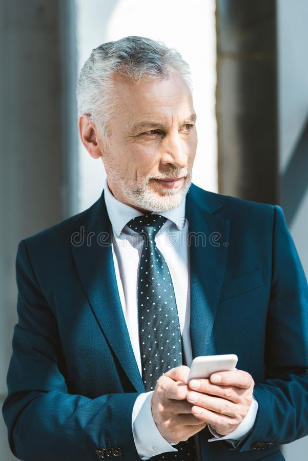 Smiling senior businessman holding smartphone. And looking away stock photos