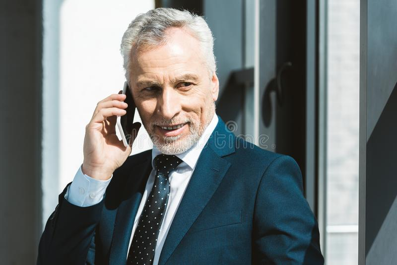 Smiling senior businessman talking by smartphone. And looking away royalty free stock photo