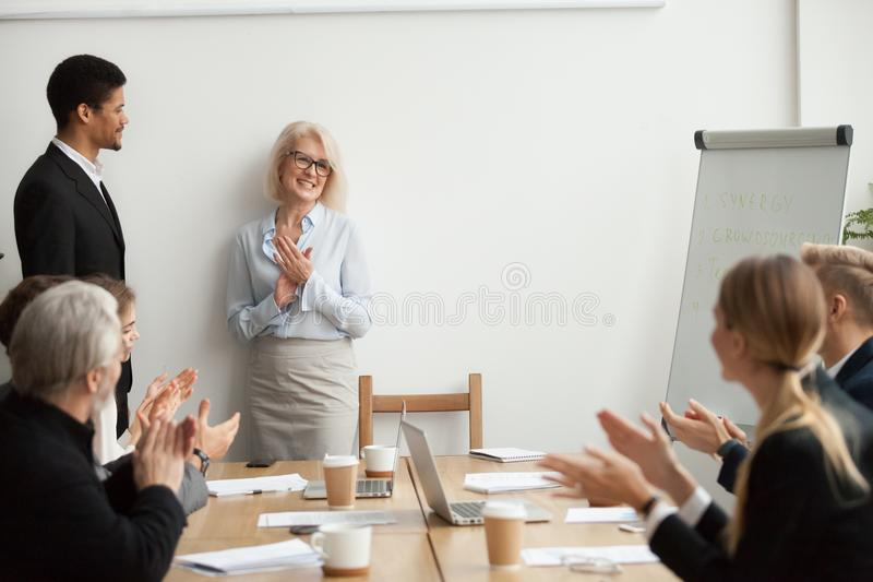 Smiling senior businesswoman boss and team clapping hands at mee royalty free stock photos