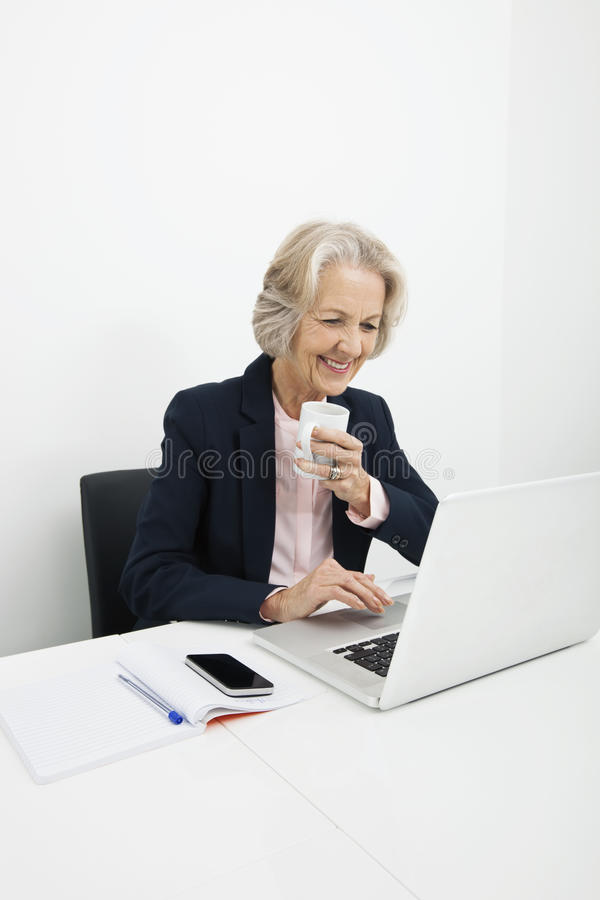 Download Smiling Senior Businesswoman Having Coffee While Using Laptop At Desk In Office Stock Photo - Image of person, corporate: 35902918