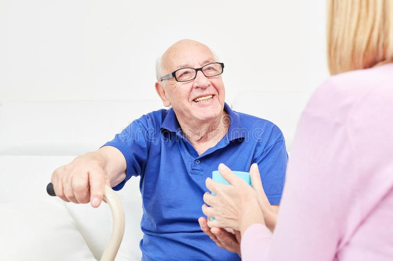 Smiling senior is cared for in home care royalty free stock photo