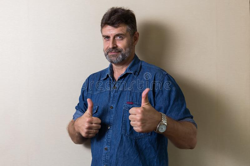 Smiling senior caucasians man relaxing. In home and make thumbs up stock photo