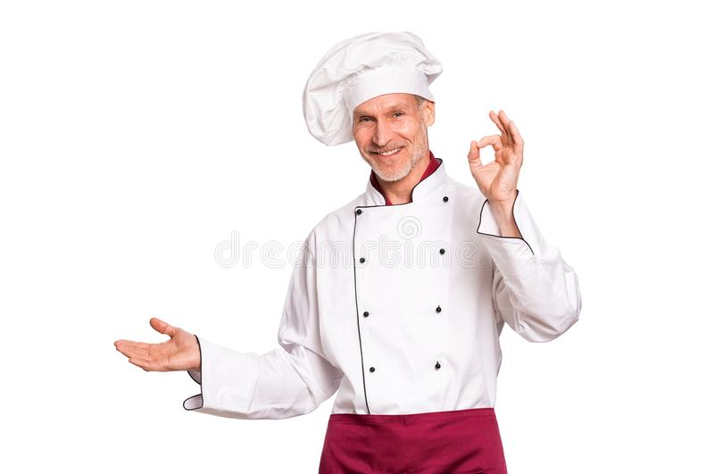 Happy chef pointing. Smiling senior cook showing something isolated on white background. Portrait of happy mature chef presenting over white background. Cheerful royalty free stock photo
