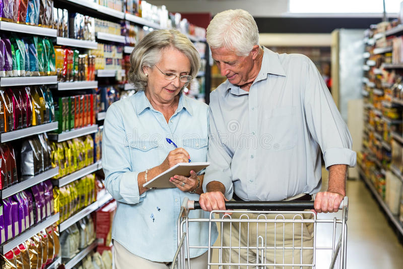 Smiling senior couple with cart checking list stock photos
