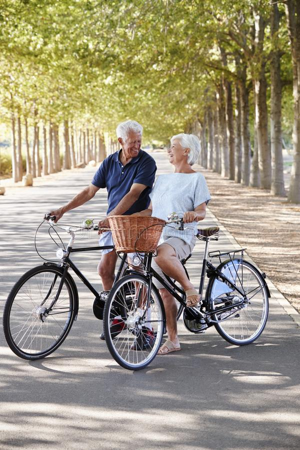 Smiling Senior Couple Cycling On Country Road stock photography