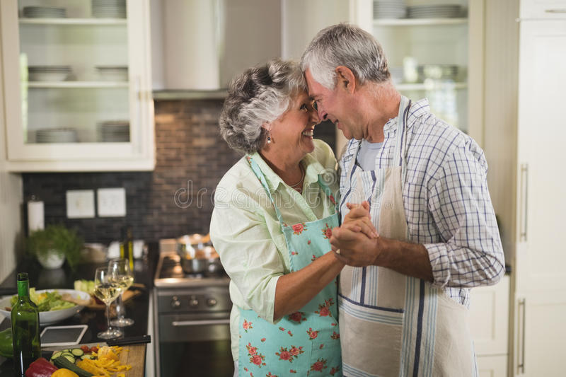 Smiling senior couple dancing in kitchen stock images