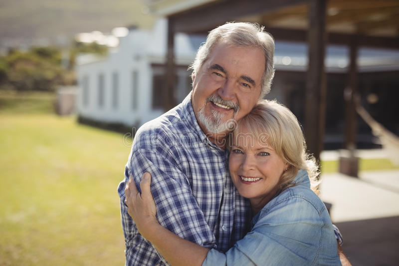 Smiling senior couple embracing each other in garden stock photography