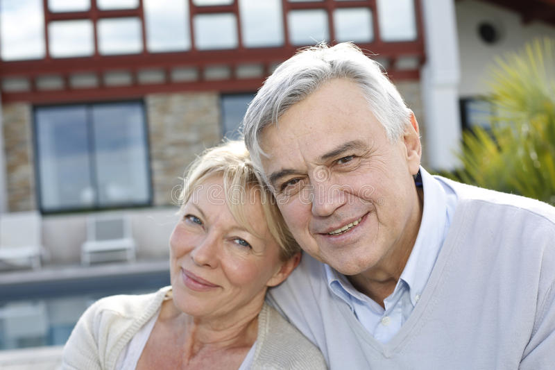 Smiling senior couple in front of home stock photography