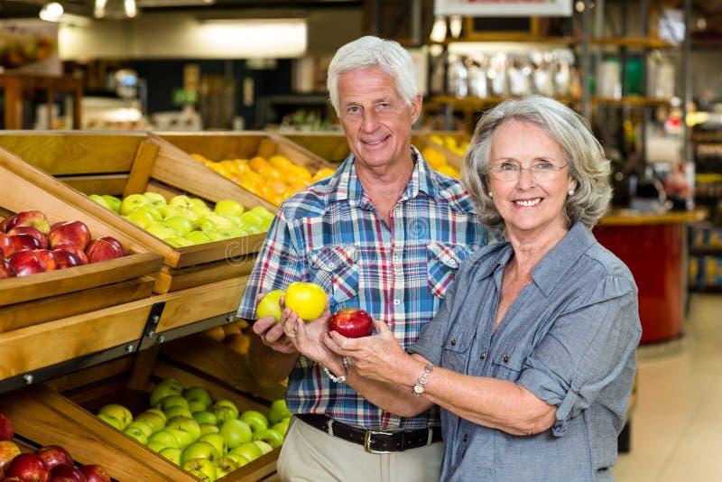 Smiling senior couple holding apples royalty free stock photo