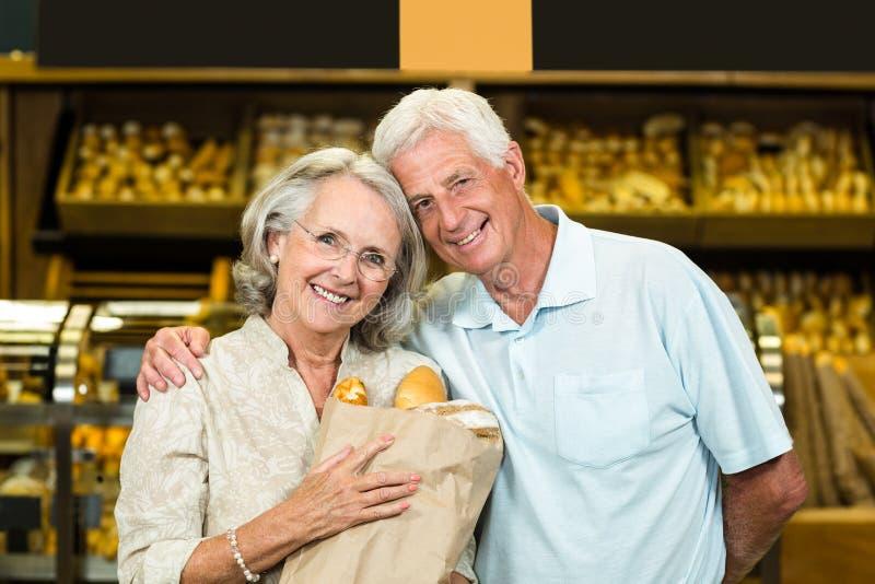 Smiling senior couple holding bakery bag stock images