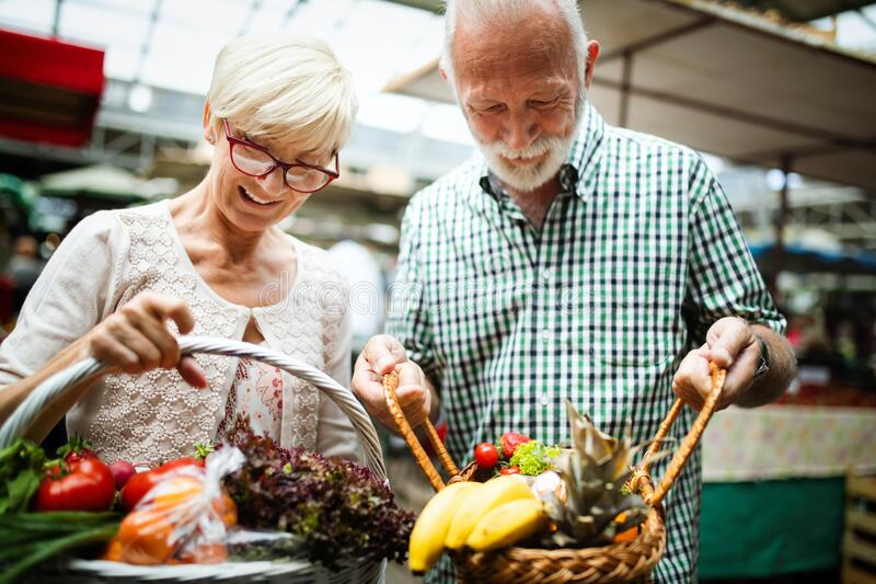 Smiling senior couple holding basket with vegetables at the market royalty free stock images