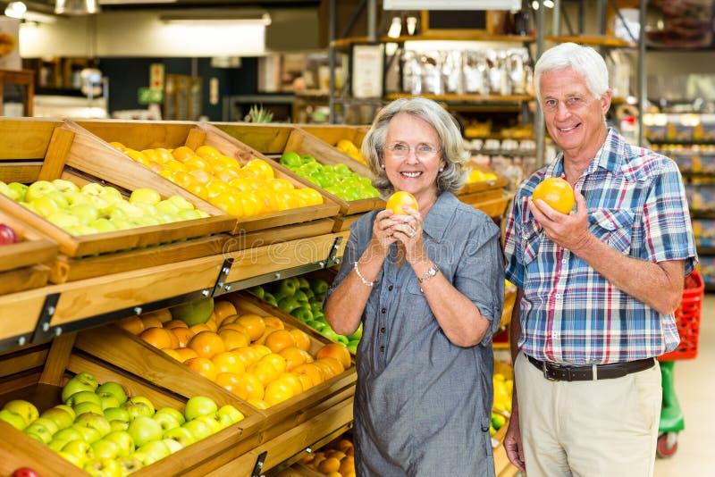 Smiling senior couple holding oranges stock photos
