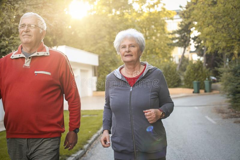 Smiling senior couple jogging in city park. royalty free stock photography