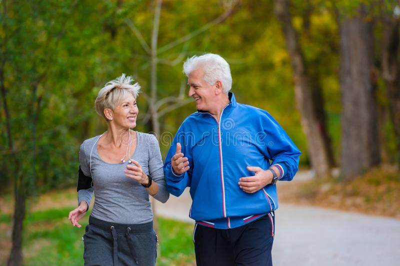 Smiling senior couple jogging in the park stock images