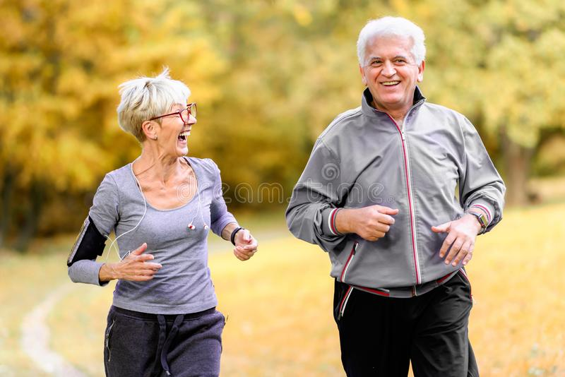 Smiling senior couple jogging in the park royalty free stock images