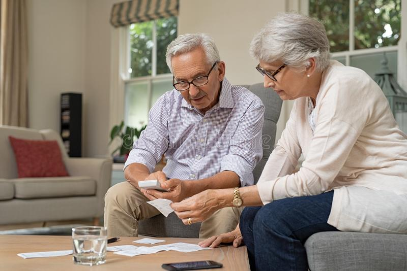 Senior couple calculating expenses. Smiling senior couple with papers, calculators and bills at home. Senior couple calculating taxes at home. Mature men and stock photos