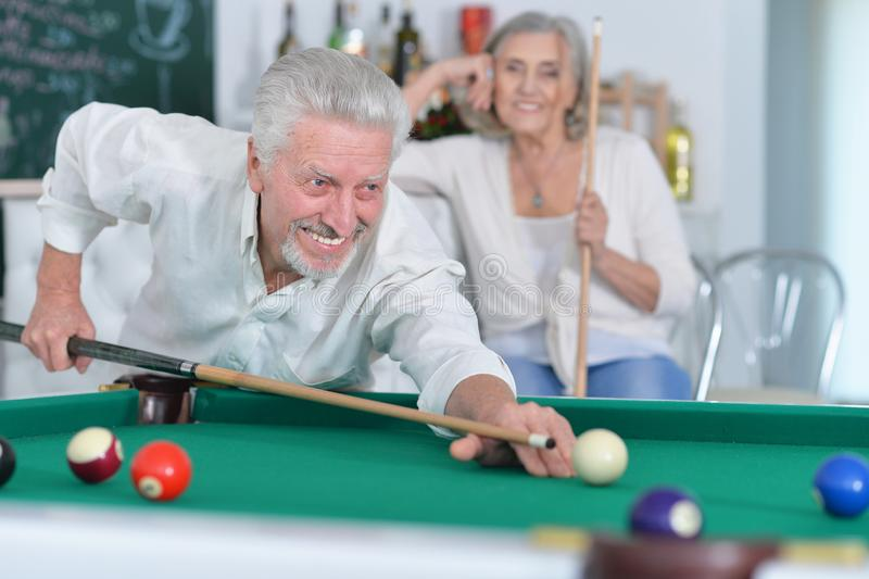 Portrait of senior couple playing billiard together royalty free stock photos