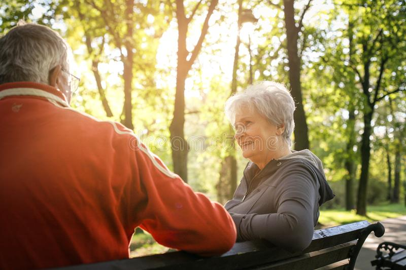 Senior couple sitting on bench after exercising and having conversation. stock images