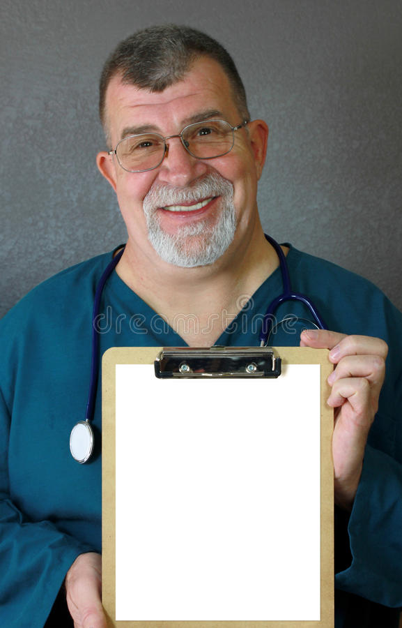 Smiling Mature Doctor Displays a Blank Clipboard royalty free stock photo