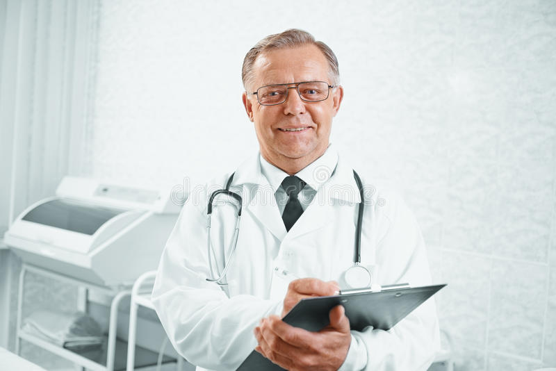 Smiling senior doctor. Portrait of older smiling man doctor with documents in hospital royalty free stock photo