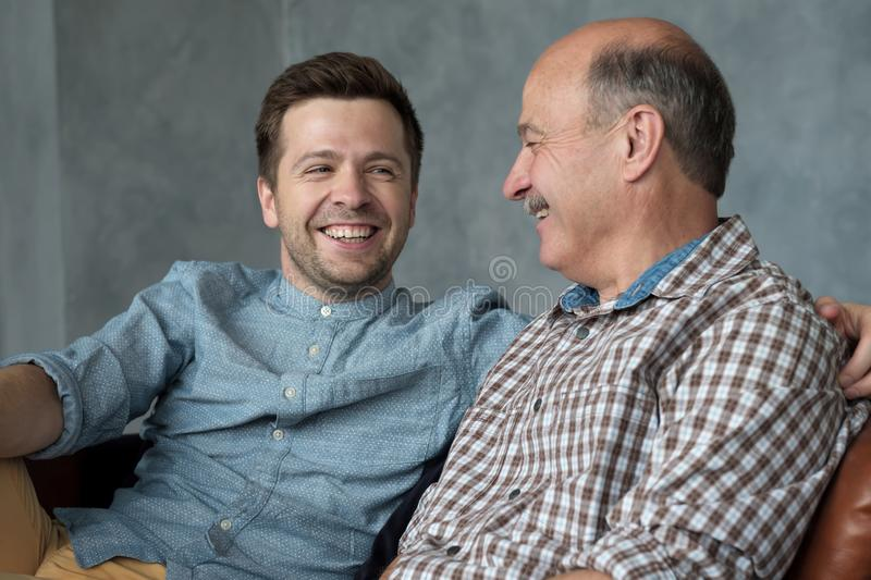Smiling senior father sit on couch talk chat with millennial son spend time at home together stock photos
