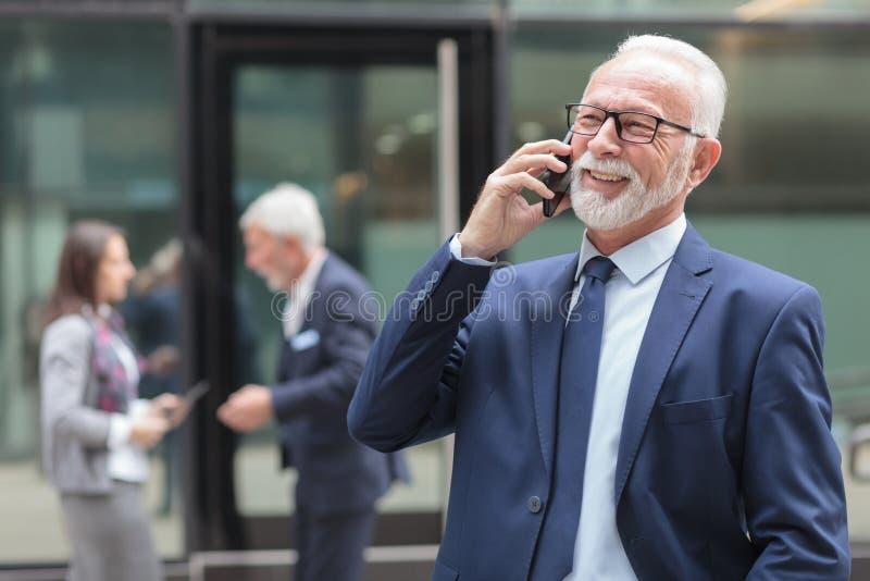 Smiling senior businessman talking on the phone on the street. Smiling senior gray haired businessman talking on the phone, standing in front of an office royalty free stock photo